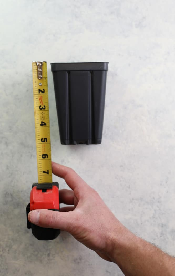 one quart plastic nursery container with tape measure next to it showing it is 6'' high.