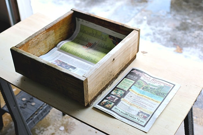 wooden box with newspaper on the bottom. The box and newspaper on resting on top of a wooden table. There is also a stack of newspaper next to the box