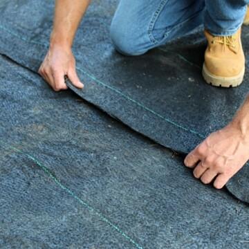 man laying woven landscape fabric