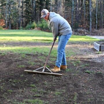 man raking dirt in bare spot of lawn to prepare soil for dormant seeding