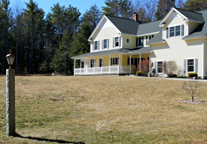 brown dormant grass in front lawn of large yellow house